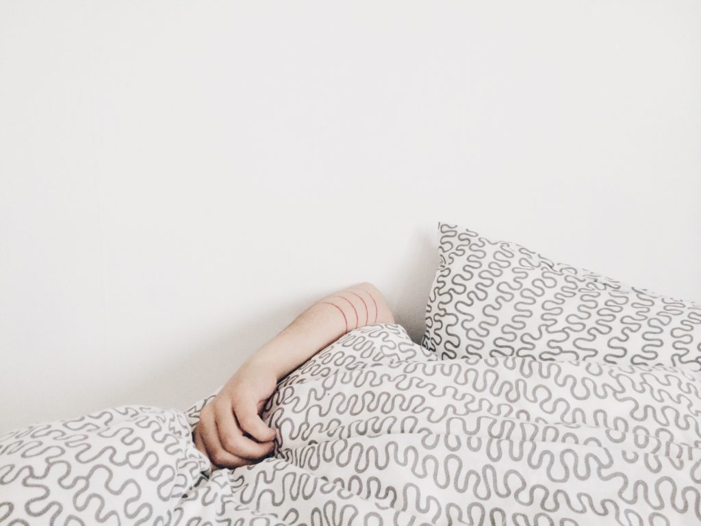Picture of a person sleeping under the covers in bed with only one arm out