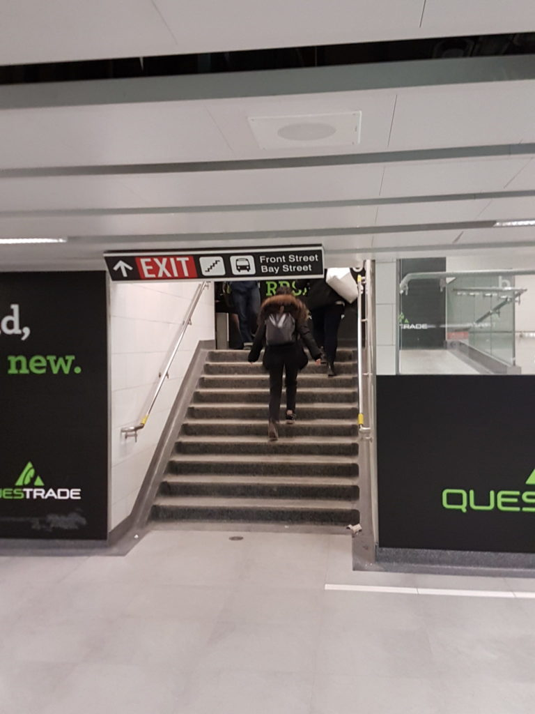 "Stairs in Toronto subway Union Station with a sign above them saying ""Exit - Front Street, Bay Street"""