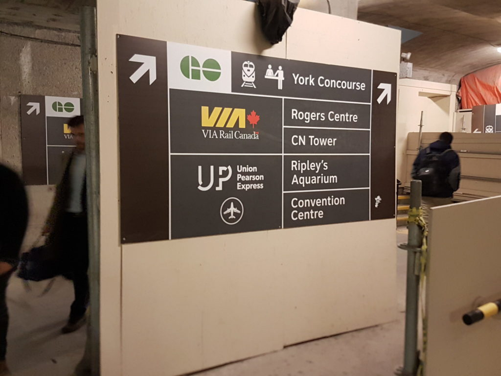 Toronto subway system sign with an arrow pointing to the right, directing people to the GO station, York Concourse, Rogers Centre, CN Tower, Ripley's Aquarium and the CN Tower
