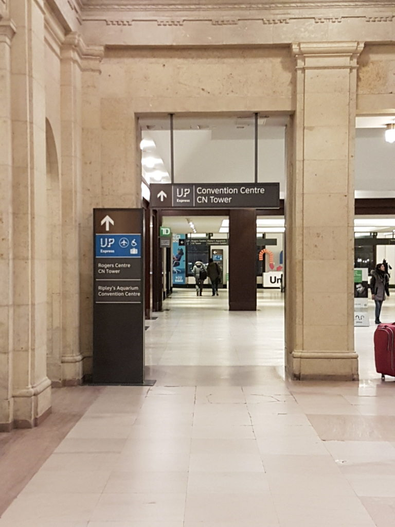 Large hallway in Toronto Union Station with signs pointing to the CN Tower and Ripley's Aquarium