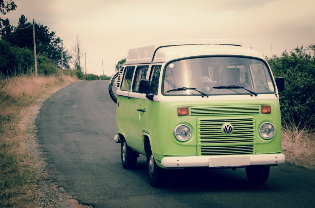 A green VW campervan driving down a curved road
