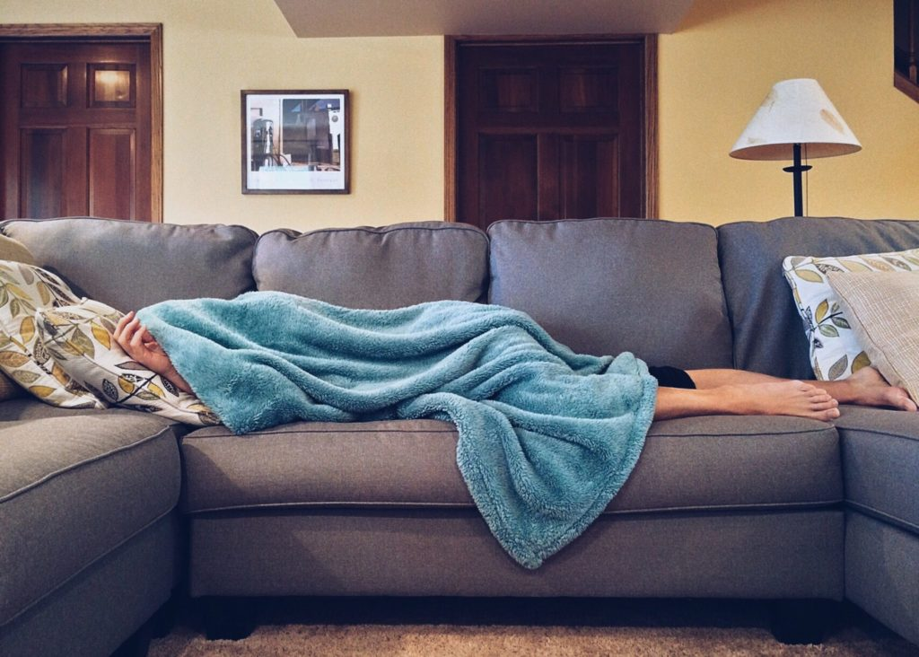 Person taking a career break sleeping on the couch under a blanket