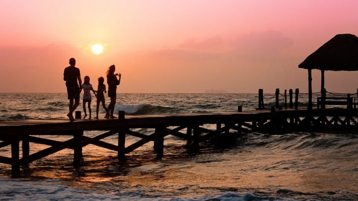 a family on a gap year walking on a pier at sunset