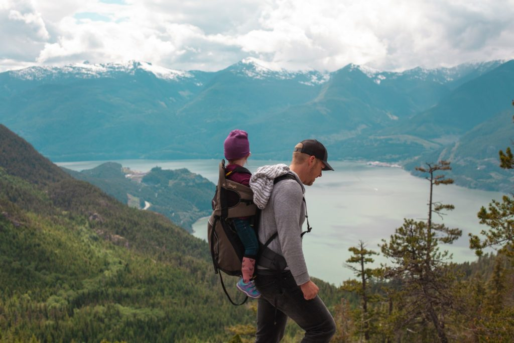 A man carrying a child in a backpack while hiking in the mountains