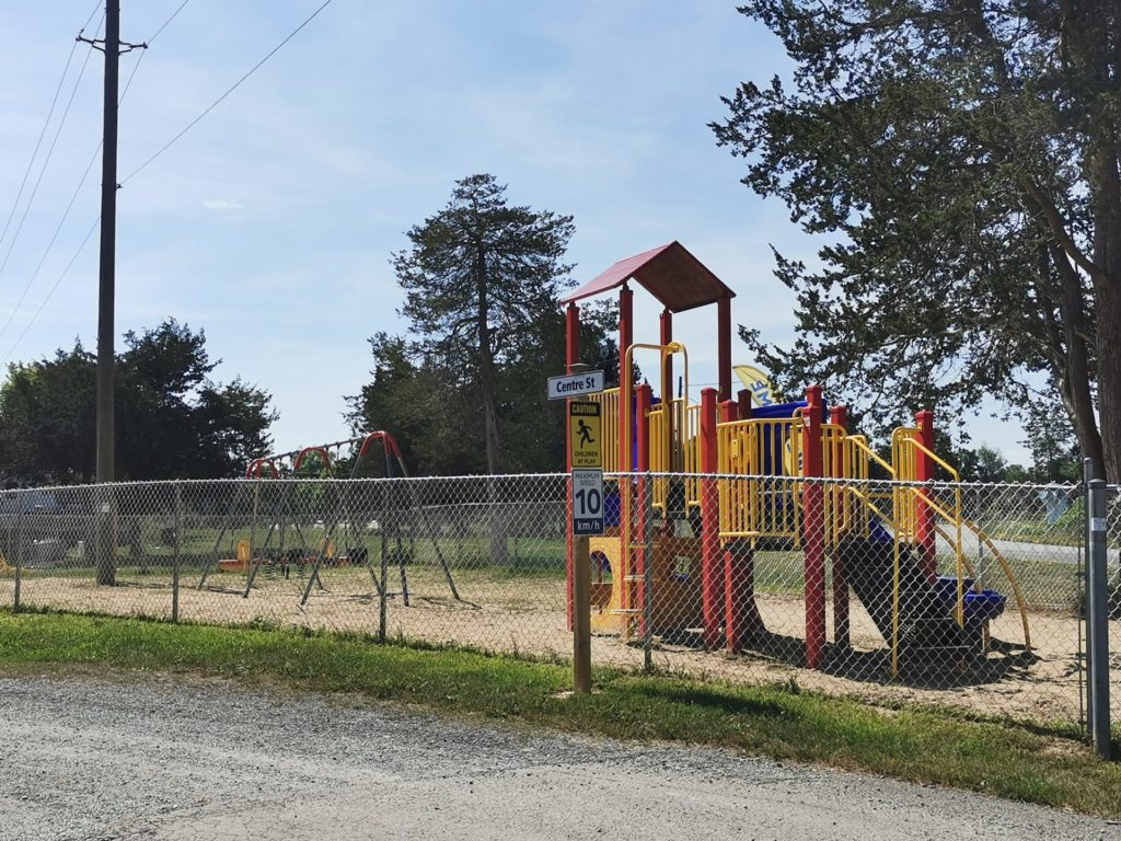 Playground structure with swingset behind