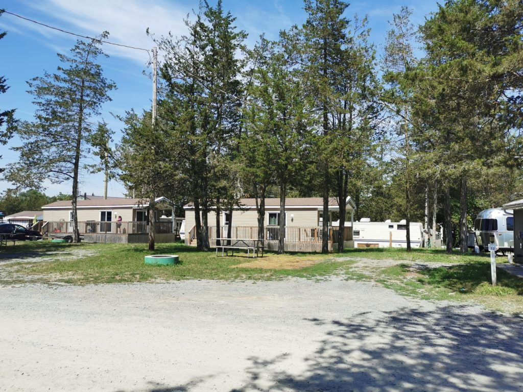 A back-in RV site with gravel pad, in full sun, with a cabin behind it